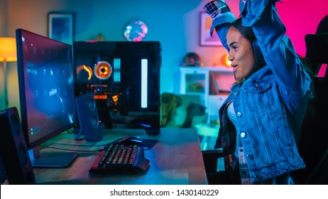 Pretty and Excited Black Gamer Girl in Headphones is Winning in First-Person Shooter Online Video Game on Her Computer and Puts Hands Up. Room and PC have Colorful Neon Led Lights Cozy Evening at Home