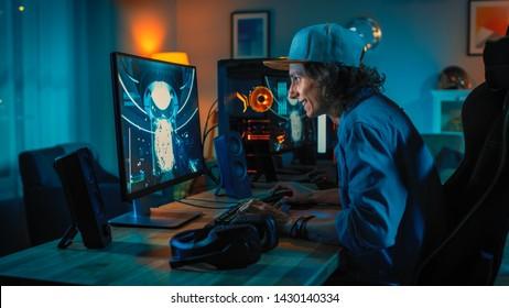 Professionele gamer first-person shooter online videogame spelen op zijn krachtige personal computer. Kamer en pc hebben kleurrijke neon led-verlichting. Jonge man draagt een pet. Gezellige avond thuis.
