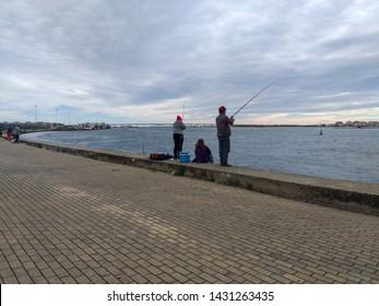 zwei Fischer, die am Fluss Aveiro fischen