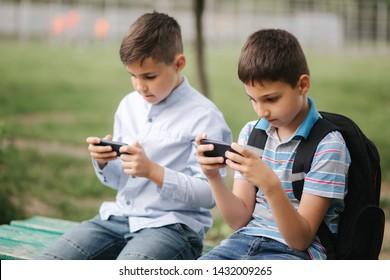 Dos niños sentados en el banco y jugar juegos en línea. Un niño con mochila. Los muchachos usan sus teléfonos