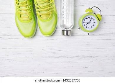 フィットネスのコンセプト、緑のスニーカー、目覚まし時計と木製の背景に淡水のボトル、上面図、健康的なライフスタイル、朝のトレーニング