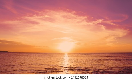 Red sundown sea. The coast of the Caribbean Sea, the yellow sun touches the horizon, beautiful orange clouds around the sun. Amazing view from the beach to the red sundown sea. Beautiful sea landscape