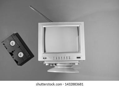 Retro Welle, Minimalismus 80er Konzept. Retro-TV mit Antenne, Videokassette. Schwarzweiss-Foto. Draufsicht