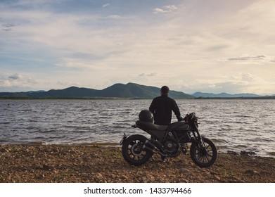 Jonge fietser die zich aan kant van grote fiets bevindt met bezienswaardigheden bij natuurlijk reservoir