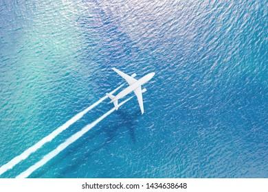 海の上を飛んでいる飛行機は白い煙の跡、水面に影を残します