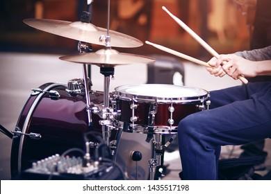 Guy ist ein Straßenmusiker in blauen Hosen, der Rhythmus auf einem wunderschönen roten Schlagzeug mit hölzernen Trommelstöcken spielt