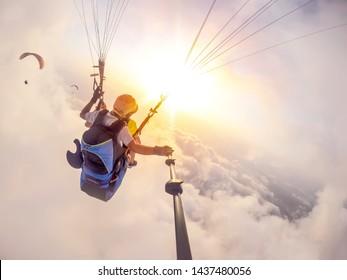 Gleitschirmfliegen am Himmel. Paraglider Tandem fliegt über das Meer mit blauem Wasser und Bergen an einem hellen sonnigen Tag. Luftaufnahme des Gleitschirms und der blauen Lagune in Oludeniz, Türkei. Extremsport. Landschaft