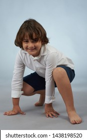 Small kid in spider man pose on gray studio background
