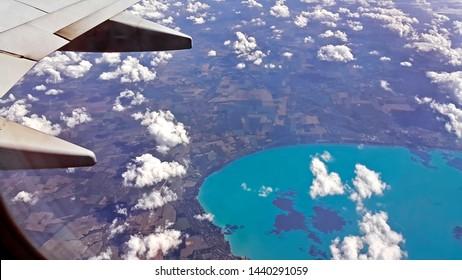 地球の風景、ハンガリーのバラトン湖、翼の一部を見下ろす飛行機の窓からの美しい壮観な眺め。高さ10キロの雲の上を飛行します。