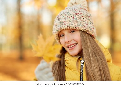 childhood, season and people concept - portrait of happy girl with maple leaf at autumn park