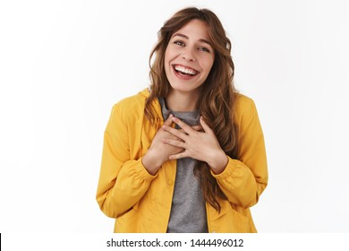 Sop sweet thank you dearly. Charming cheerful gorgeous young european girl press hands heart chest smiling express gratitude delight grateful awesome touching gift, standing white background