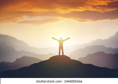 Man erfolgreich wandernde Kletterschattenbild in den Bergen, Motivation und Inspiration im schönen Sonnenuntergang. Klettererarme ausgestreckt auf Berggipfel mit Blick auf inspirierende Landschaft.