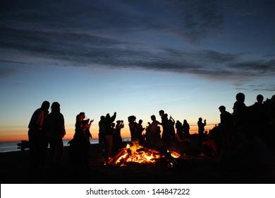 火の隣のビーチで夕方に祝う人々