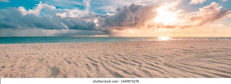 Nahaufnahme des Sandes am Strand und am blauen Sommerhimmel. Panorama Strandlandschaft. Leerer tropischer Strand und Seelandschaft. Orange und goldener Sonnenuntergangshimmel, weicher Sand, Ruhe, ruhiges entspannendes Sonnenlicht, Sommerstimmung