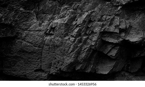 Dark Aged Shabby Cliff Face und geteilt durch riesige Risse und Schichten. Grobe, raue graue Stein- oder Felsstruktur von Bergen, Hintergrund und Kopierraum für Text über Themengeologie und Bergsteigen.