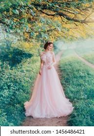 優しい笑顔の女の子、森のエルフの妖精が小道を歩く、魅力的な若い赤毛のかわいい花嫁、床に長く緑豊かなチュールピンクのドレス、創造的な色の青緑色の草の木。クイーンクラウン。グラマースタイルのファッション