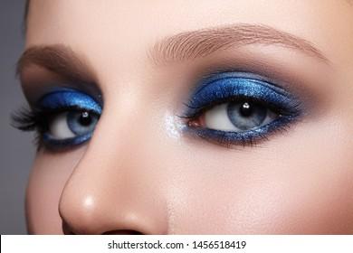 青い目のメイクで女性の顔のクローズアップマクロ。ファッションはメイクアップ、輝くきれいな肌、完璧な眉の形を祝います。シャイニーシマーとルージュ