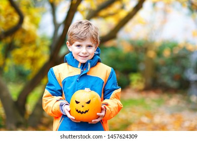 Happy cute little kid boy with halloween pumpkin lantern. Funny child in colorful clothes having fun and playing in autumn garden on cold autumnal day. Scary jack-o-lantern, celebration of holiday.
