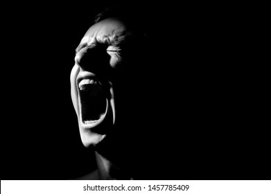black and white photo on a black background, distorted face screaming