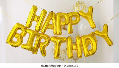 Palabras de feliz cumpleaños doradas hechas de globos inflables sobre fondo blanco.