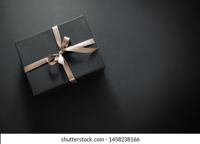 One gift wrapped in dark black paper with luxury bow on dark background. Horizontal with copy space.