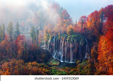 Incredible view on foggy waterfall in Plitvice lakes. Orange autumn forest on background. Plitvice National Park, Croatia. Landscape photography