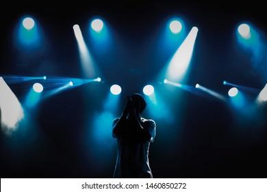 Cool jonge rapzanger met microfoon op helder verlicht podium in heldere blauwe lichten. Hip hop ster uitvoeren solo ingesteld op scène in music hall. Populaire rapper zingt een lied op rockfestival in nachtclub