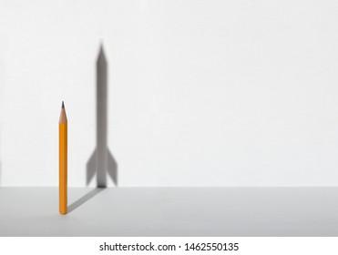 Lápices y una sombra en forma de nave espacial. Concepto de negocio de éxito, curador y resolución de problemas. Copie el espacio para el texto.