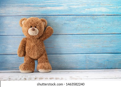Lindo oso de peluche con espacio de copia sobre fondo de madera de color azul.