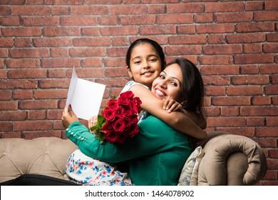 Moederdag - Indisch meisje / moeder die Moederdag vieren met Rose Flower Bouquet, wenskaart terwijl ze elkaar knuffelen en kussen
