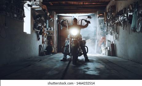 Motorista estadounidense con su motocicleta en el garaje. helicóptero fresco y potente que el motorista recogió con sus propias manos