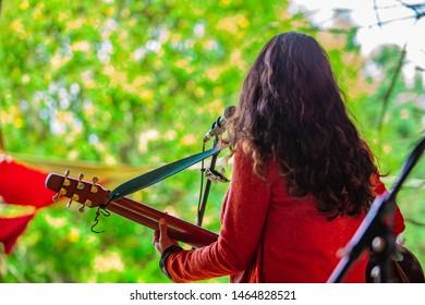 文化と現代の音楽イベントの融合。自然の中でライブ音楽のギグ中に歌ったりギターを弾いたりする女性ミュージシャンを後ろから見たところ、背景にぼやけた木の葉が見えます