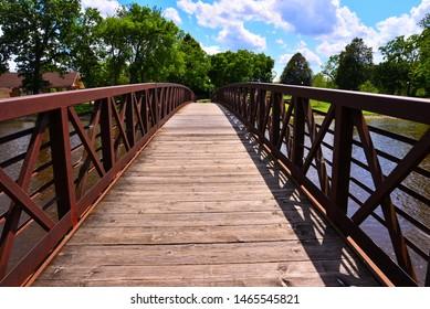 ウィスコンシン州バーリントンにあるフォックス川に架かる長距離の交通橋で、曇った青い空の下の公園へと続いています。