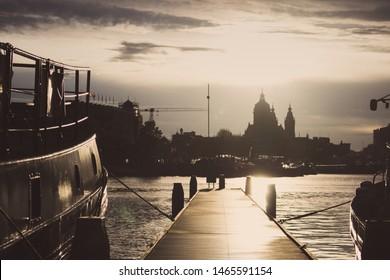 Holzpier mit Booten bei Sonnenuntergang im Amsterdamer Dock. Amsterdamer Stadtschattenbilder im Abenddämmerungslicht. Kathedralenschattenbild am Abendhimmel in den Niederlanden. Innenstadt in Amsterdam Dock.