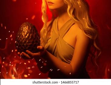 Schonende Silhouette der blonden Frau der Fantasiekunstwerk-Nahaufnahme ohne Gesichtshände, die großes Drachenei halten. Karneval Halloween Inspiration von Cosplay Daenerys Targaryen. Hintergrund rotes Feuergelb funkeln Licht