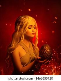 Eine junge blonde Frau hält ein großes, ungewöhnliches Drachenei in den Händen. Sie sieht ihn hoffnungsvoll an. Hintergrund rot flammendes Feuer mit Rauch und Funken. Studio kreative Fotografie Daenerys Targaryen