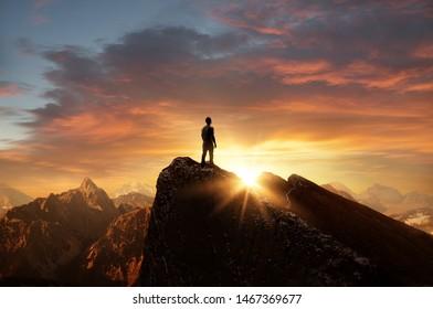 Ein Mann, der auf einem Berg steht, als die Sonne untergeht. Ziele und Erfolge Konzept Foto Composite.