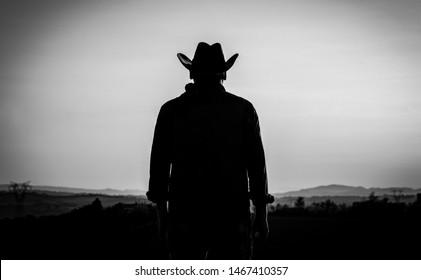 日没の夜に田舎でカウボーイハットをかぶった現代のカウボーイ-シルエット-アメリカのカウボーイ