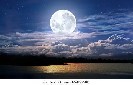 満月と夜の湖の曇り空