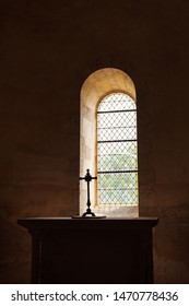 Cross silhouette on altar near window in dark empty old chapel. Game of light and shadow in church. Religious christian background. Despair and hope,  divine mercy, god love concept.