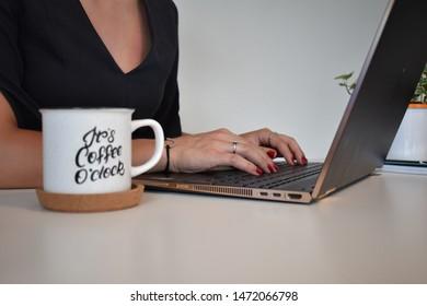 オフィスで彼女のビジネスブログに取り組んでいて、コーヒーを飲む女の子