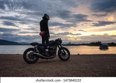 Fietser die zich op uitstekende grote fiets met kleurrijke hemel bij reservoir bevindt