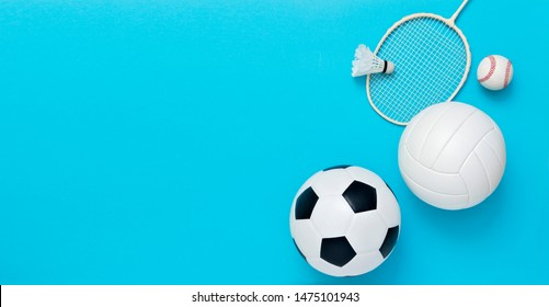 Assorted sports equipment including a soccer ball, volleyball, baseball, badminton racket on a light blue background