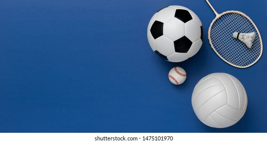 Assorted sports equipment including a soccer ball, volleyball, baseball, badminton racket on a blue background