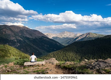 Joven excursionista o turista sentado en un banco apreciando la increíble vista del paso de la independencia en las Montañas Rocosas de Colorado, EE.