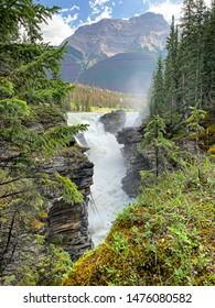 Bergwasserfälle zwischen schroffen felsigen Klippen voller Kiefern, aufsteigendem Wassernebel und Bergen im Hintergrund.