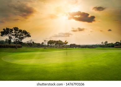 A view landscape green grass at golf course , big trees with black cloud  sunlight rays sky background.