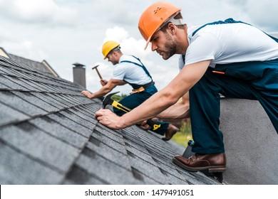 同僚と屋根を修理するハンサムな便利屋の選択的な焦点