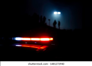 Polizeilichter blinken, während Menschen im Hintergrund silhouettiert werden, während eine Straßenlaterne von oben leuchtet.