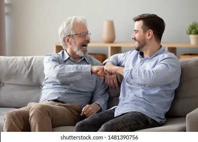 Elderly grey haired man and handsome guy giving fist bump, old father rejoices of grown up son successes congratulates him feels happy, unity respect gesture good relations diverse generations concept